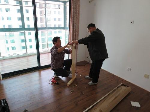 (写真2)ベッドフレームの組立、ジャケットを着た作業員
