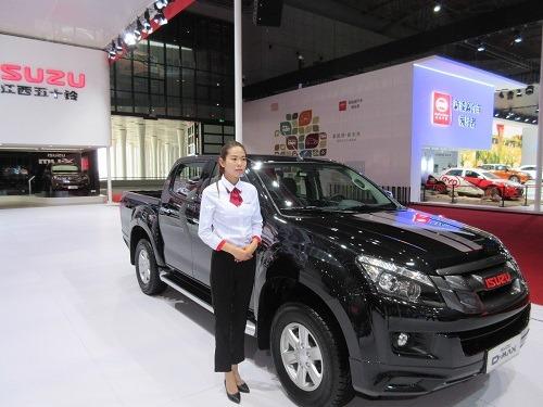 (写真4)ISUZUの展示車のとなりに立つ女性スタッフ