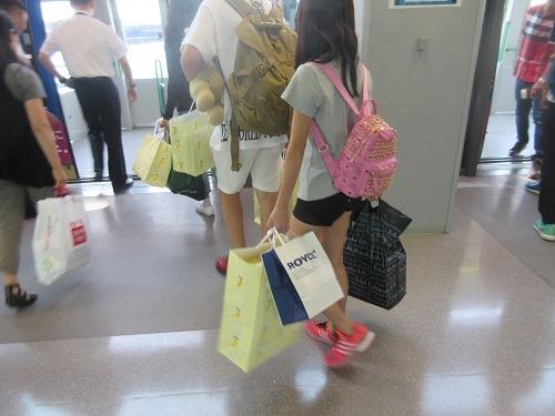 (写真3)空港内で両手いっぱいに商品を買い込んだ中国人たち(関西空港)