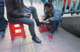 (写真1)路上で靴磨きをしているおばさん(広州市内)
