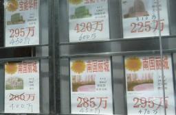 (写真1)手書きで書き換えられる中古マンション価格(広東省深セン市)