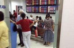 (写真1)証券会社の株価ボードを眺める投資家たち(上海市内)